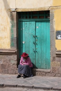 An elderly lady resting in a doorway on a back alley in Cuzco